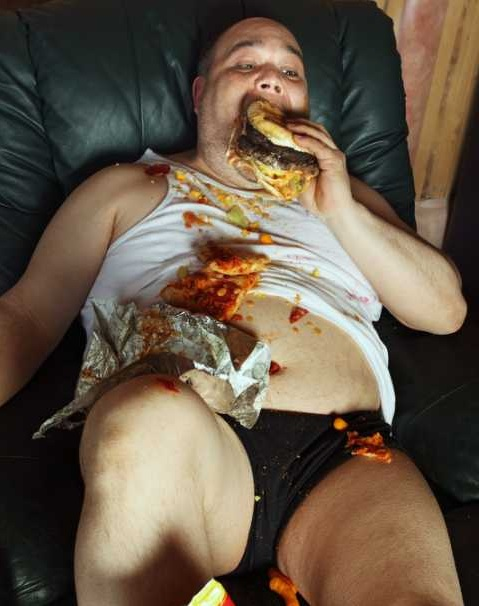 fat guy eating food on couch