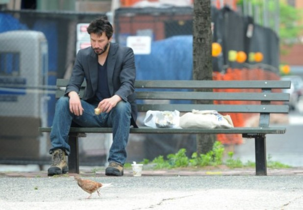 Keanu Reeves sitting alone on bench